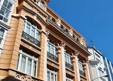 """Edificio firmado por Rodolfo Ucha en 1925. Su estilo es ecléctico, entre el modernismo y el funcionalismo. En el interior sobresale la """"Sala de Conversaciones"""", popularmente conocida como """"La Pecera"""", logrando un conjunto decorativo único en Galicia obra de Bello Piñeiro."""